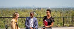 Three students sitting on balcony of CELS overlooking NYC skyline.