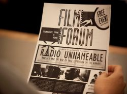 Individual holding a flyer for a free film institute event.