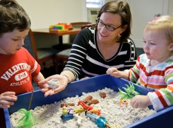 Staff at Montclair State University Center for Autism working with children at a sandbox sensory table.