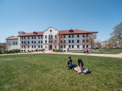 exterior shot of Russ Hall on a sunny day with a few students in the quad