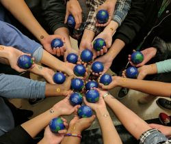 Multiple hands coming into the center holding stress balls