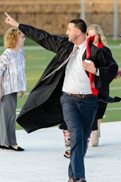 Student in graduation robe waving to off-camera friend.