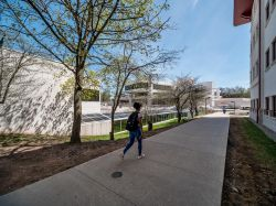 A student walking in between the Student Center and the Graduate School.