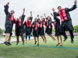 A bunch of graduating students jumping up in the air.
