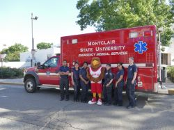 Montclair State EMS posing for a photo in front of an ambulance with Rocky.
