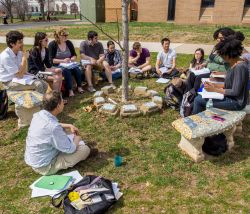 Photo of a classroom in an outdoor setting with faculty and students sitting on benches and the ground.