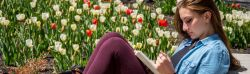 woman reading with flowers in background