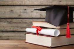 Image of a stack of books with a diploma and a graduation cap.