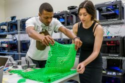 Male and female student look at green, 3D printed dress in MIX Lab