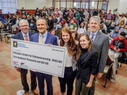 Two women students, and three men, stand with $500,000 check payable to Feliciano Center for Entrepreneurship, with crowd in the background.