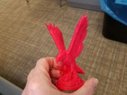 Hand holding a small 3D-printed Red Hawk statue