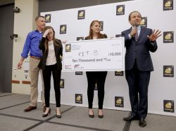 Two female students stand with $10,000 oversized check, with two male judges, at pitch contest