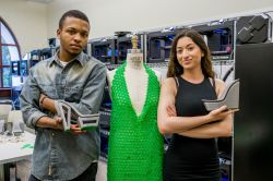 Male and female student pose with 3D printed green dress, and gray shoes