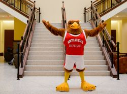 Red Hawk mascot stands in atrium of business school building