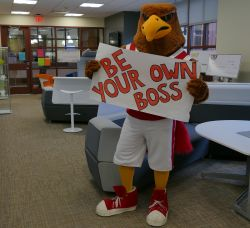 "Mascot Rocky with ""Be Your Own Boss"" sign inside Feliciano Center"