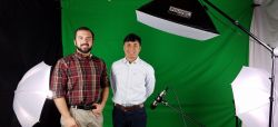 Two male students in video studio, in front of a green screen
