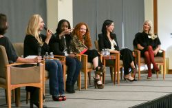 Six women in chairs on stage for the panel