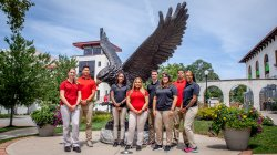 Photo of MS in Athletic Training students standing in front of Rocky statue on campus.