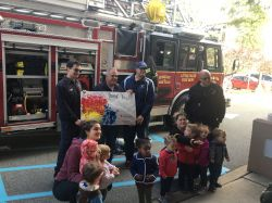 Young children posing with Little Falls Fire Fighters and fire truck