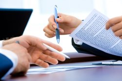 close up of hands holding pens and paper as two people discuss paperwork at a desk.