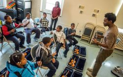 University Americorps volunteers teaching music class to kids.