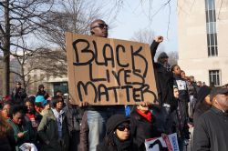 Man holding Black Lives Matter sign amidst protest.