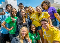 Group of 11 smiling students wearing various colors of MSU branded t-shirts