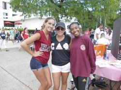 Three students posing for a picture in their Greek gear in the quad.