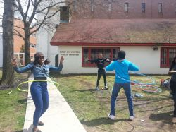 Three students hula hooping outside the Drop In Center