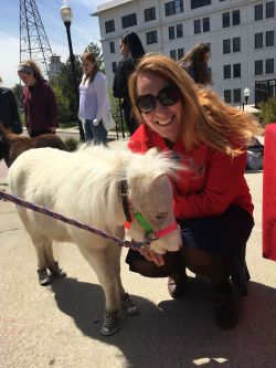 Marie Cascarano outside on a sunny day with a white mini horse smiling