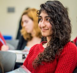 Photo of a smiling student sitting in a class.