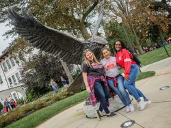 Students standing by the Red Hawk Statue