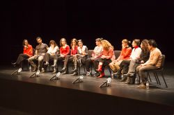 Image from Le Sorelle Macaluso event with a group people lined up on stage sitting in chairs.