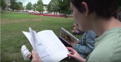 Image of high school student sitting on grass outside reading an Italian book