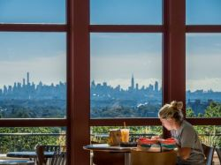 Student reading in CELS overlooking NYC Skyline