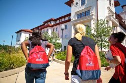 New students walking towards building wearing Montclair State branded bags.