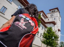 Photo of student with Montclair State Red Hawks themed backpack and pins.
