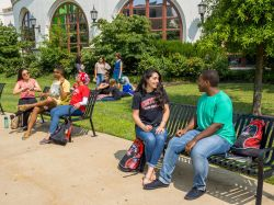 Students talking while sitting on campus benches.