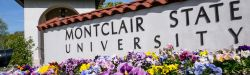 Signage of Montclair State University entrance amidst flowers.