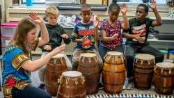 Children beating drums with instructor