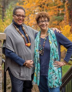 Delores McMorrin and Lorraine Whitaker posing outdoors in fall folliage