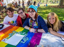 Four Montclair State University students sitting at LGBTQ table at fair on campus