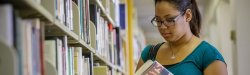 student reading book at library shelf