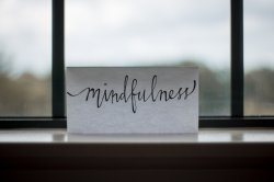 word mindfulness printed on paper near window