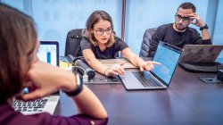 photo of female student sitting at conference table pointing to laptop screen
