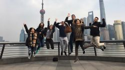 Students jumping in front of Shanghai skyline