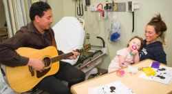 Atlantic Health System music therapist Danny Marain plays guitar for a patient and mother at the Newton Medical Center.