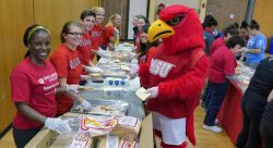 Rocky the Red Hawk joins Montclair State volunteers in making sandwiches for local homeless shelters and soup kitchens, one of the many service activities during the National Day of Service.