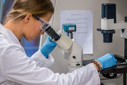 Image of student in lab clothes looking into a microscope