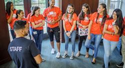 Photo of students in red shirts who are participating in Hispanic Student College Institute, talking to staff member
